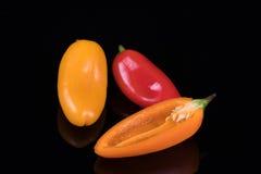 Красный цвет, желтый цвет и оранжевые сладостные перцы изолированные на черноте Стоковое Изображение
