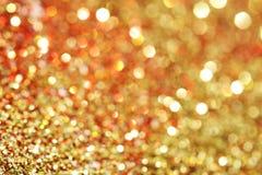 Красный цвет, золото, оранжевая предпосылка ярких блесков искры Стоковые Фото