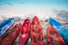 Красный цвет и голубой каяк на пляже Стоковое Изображение RF