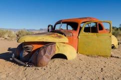 Красный цвет и желтый цвет покинули классический автомобиль в пустыне Namib около пасьянса, Намибии Стоковые Изображения RF