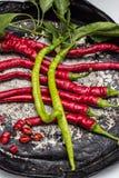 Красный цвет и 2 зеленых перца chili на старой плите Стоковая Фотография