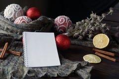 Красный цвет и украшения рождества золота и блокнот для примечаний лежат на таблице дуба Стоковые Изображения RF