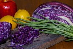 Красный цвет капусты, лимоны, зеленый цвет лука на доске с мешковиной Стоковые Изображения RF
