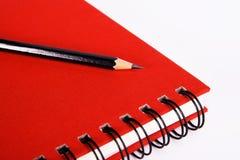 красный цвет карандаша тетради Стоковые Изображения