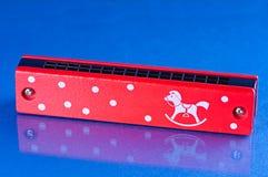 Красный цвет объекта музыки предпосылки губной гармоники картины деревянный Стоковое фото RF