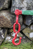 Красный цвет покрасил крюк металла против старой каменной стены Стоковые Фото