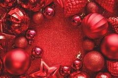 красный цвет рамки рождества Шарики, звезды, конусы и сердца рождества на красном цвете сверкнают предпосылка Плоское положение В стоковая фотография