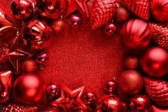 красный цвет рамки рождества Шарики, звезды, конусы и сердца рождества на красном цвете сверкнают предпосылка Плоское положение В стоковое изображение