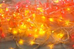 Красный цвет рождества и граница желтых светов на светлой деревянной предпосылке Стоковая Фотография RF