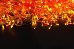 Красный цвет рождества и граница желтых светов на светлой деревянной предпосылке Стоковые Изображения