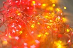 Красный цвет рождества и граница желтых светов на светлой деревянной предпосылке Стоковое Изображение