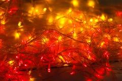 Красный цвет рождества и граница желтых светов на светлой деревянной предпосылке Стоковая Фотография