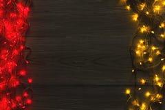 Красный цвет рождества и граница желтых светов на серой деревянной предпосылке Стоковое фото RF