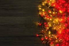 Красный цвет рождества и граница желтых светов на серой деревянной предпосылке Стоковая Фотография