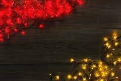 Красный цвет рождества и граница желтых светов на серой деревянной предпосылке Стоковые Изображения