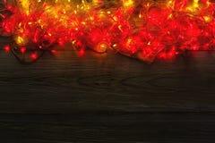 Красный цвет рождества и граница желтых светов на серой деревянной предпосылке Стоковое Изображение RF
