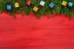 красный цвет рождества предпосылки Ель рождества с декоративными подарками на красной деревянной предпосылке Стоковые Изображения RF