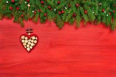 красный цвет рождества предпосылки Ель рождества с декоративным сердцем на красной деревянной предпосылке Стоковое фото RF