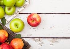 Красный цвет розовой дамы королевский торжественный и кузнец бабушки зеленеют яблока в винтажной коробке на деревянной предпосылк стоковая фотография
