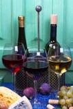 Красный цвет, розовые и белые стекла и бутылки вина Виноградина, смоква, гайки и листья на старой голубой таблице Стоковые Изображения RF