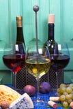 Красный цвет, розовые и белые стекла и бутылки вина Виноградина, смоква, гайки и листья на старой голубой таблице Стоковая Фотография RF