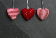 Красный цвет сделал по образцу сердца валентинки влюбленности вися на сером ston шифера Стоковое Фото