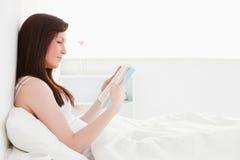 красный цвет чтения книги женский с волосами милый стоковое фото