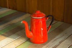 Красный чайник на деревянном столе стоковые фото