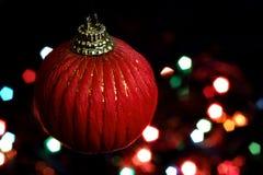 Красный шарик рождества против предпосылки красочных светов Стоковое Изображение RF