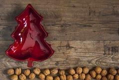 Красный шар в форме рождественской елки на земле грецких орехов, деревенском wo стоковые изображения