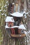 Красный birdhouse амбара предусматриванный в снеге с снегом покрыл деревья запачканные в предпосылке Стоковые Изображения RF