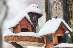 Красный birdhouse амбара предусматриванный в снеге с снегом покрыл деревья запачканные в предпосылке Стоковое Фото