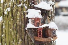 Красный birdhouse амбара предусматриванный в снеге с снегом покрыл деревья запачканные в предпосылке Стоковые Фото