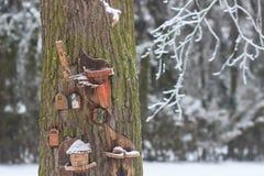 Красный birdhouse амбара предусматриванный в снеге с снегом покрыл деревья запачканные в предпосылке Стоковое Изображение RF