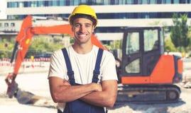 Красный earthmover с сильным латино-американским рабочий-строителем стоковое фото rf