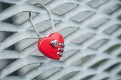 Красный padlock в форменном сердце на металлической решетке Стоковые Изображения RF