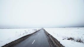 Красный sportive автомобиль начинает управлять на дороге окруженной полями предусматриванными в снеге акции видеоматериалы