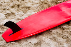 Красный surfboard на песке Стоковые Фотографии RF