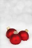 3 красных безделушки на снеге стоковое изображение rf