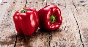 2 красных болгарского перца на старых деревянных планках Деревенское взятие стоковая фотография rf