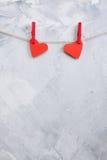 2 красных бумажных сердца вися на зажимки для белья на веревочке Стоковые Фото