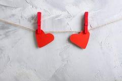 2 красных бумажных сердца вися на зажимки для белья на веревочке Стоковое Изображение RF