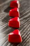 56/5000 красных в форме сердц конфет клала вне в ряд на таблицу Стоковые Фото