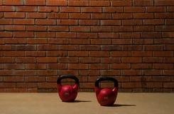 2 красных гантели для спорт стоят на поле около кирпичной стены Стоковые Фото