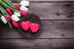 2 красных горящих свечи в форме сердца в гнезде и яркого Стоковая Фотография RF