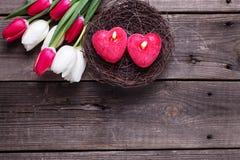 2 красных горящих свечи в форме сердца в гнезде Стоковая Фотография RF