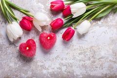 2 красных горящих свечи в форме сердца и красного и белого tuli Стоковая Фотография
