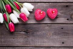 2 красных горящих свечи в форме сердца и ярких тюльпанов fl Стоковое фото RF