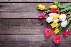 2 красных горящих свечи в форме сердца и ярких тюльпанов fl Стоковое Изображение RF