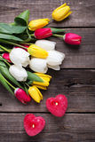 2 красных горящих свечи в форме сердца и ярких тюльпанов fl Стоковое Изображение